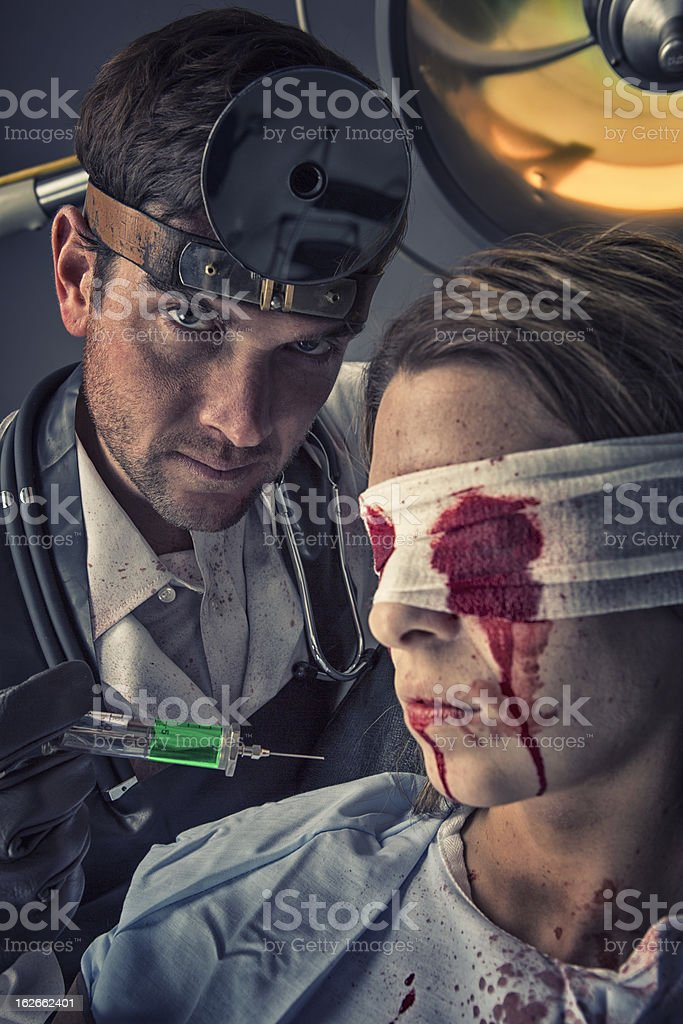 Evil Doctor trying out toxic serum on his female victim royalty-free stock photo