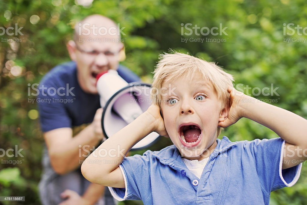 Evil father yelling at son stock photo
