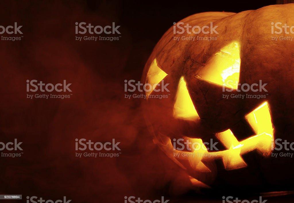 Evil Halloween pumpkin lit up with smoke black background stock photo