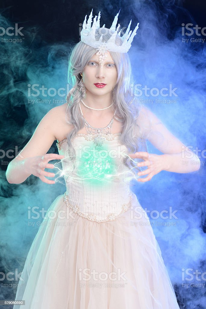 evil ice queen with ball of magic stock photo