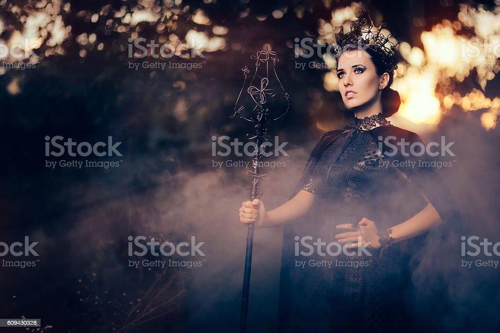 Evil Queen Holding Scepter in Misty Forest stock photo