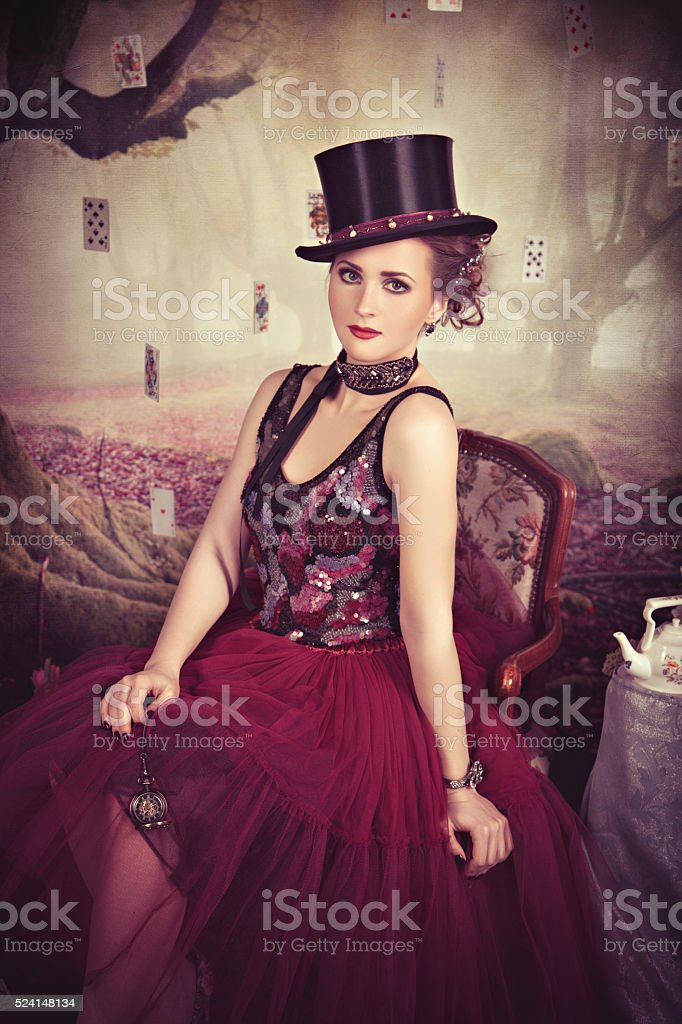 Evil Queen in bowler sitting on the armchair stock photo