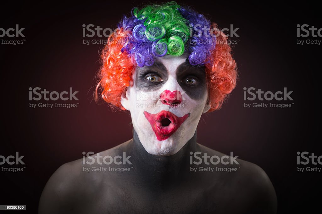 Evil Spooky Clown Portrait on dark background. expressive man stock photo