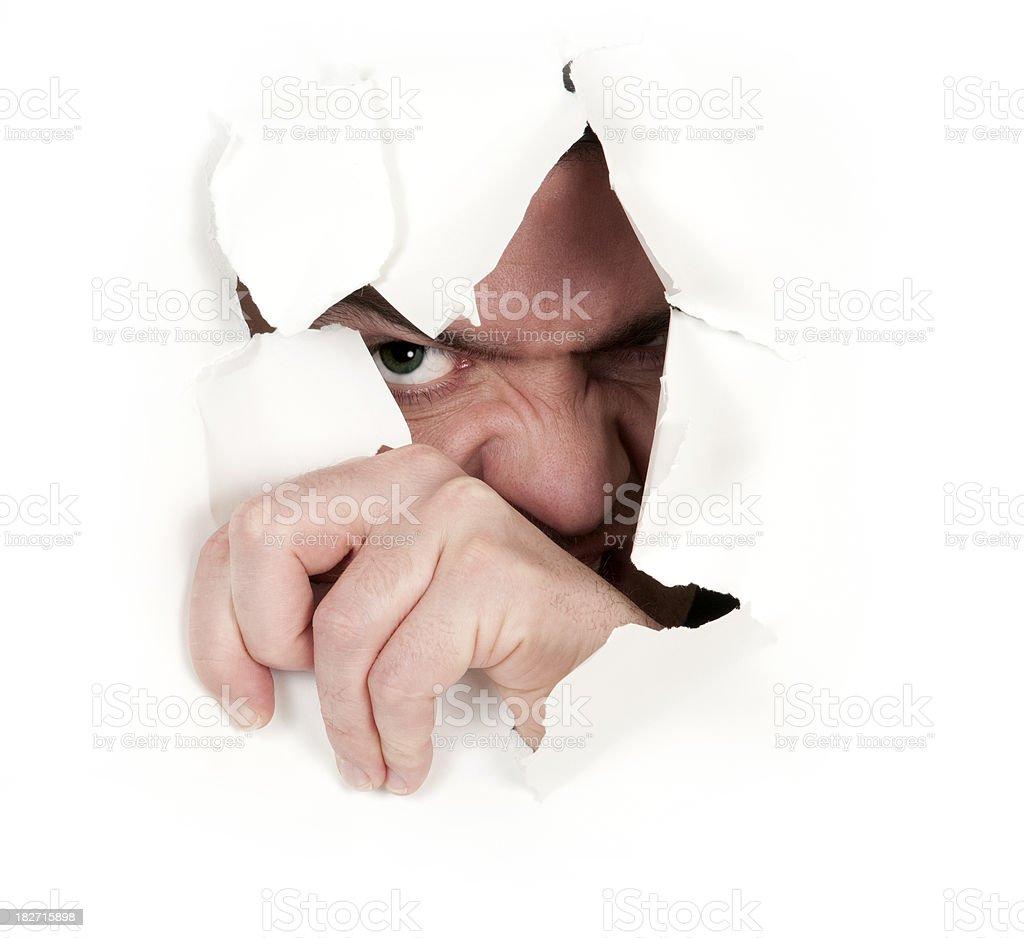 Evil spy peeks thorugh cracked white wall royalty-free stock photo