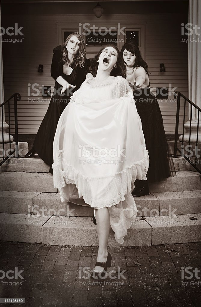 Evil Step Sisters Pushing Woman Down Stairs stock photo