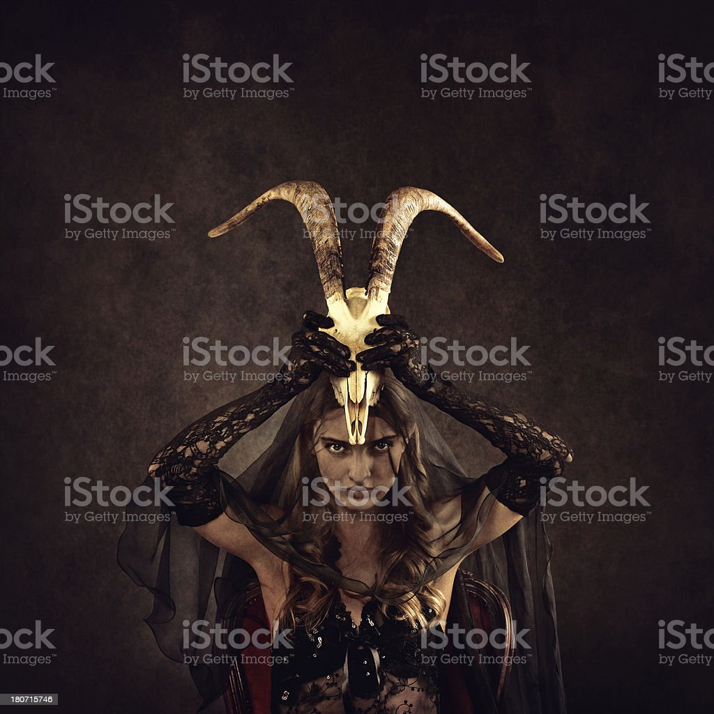 evil witch holding a goat skull stock photo