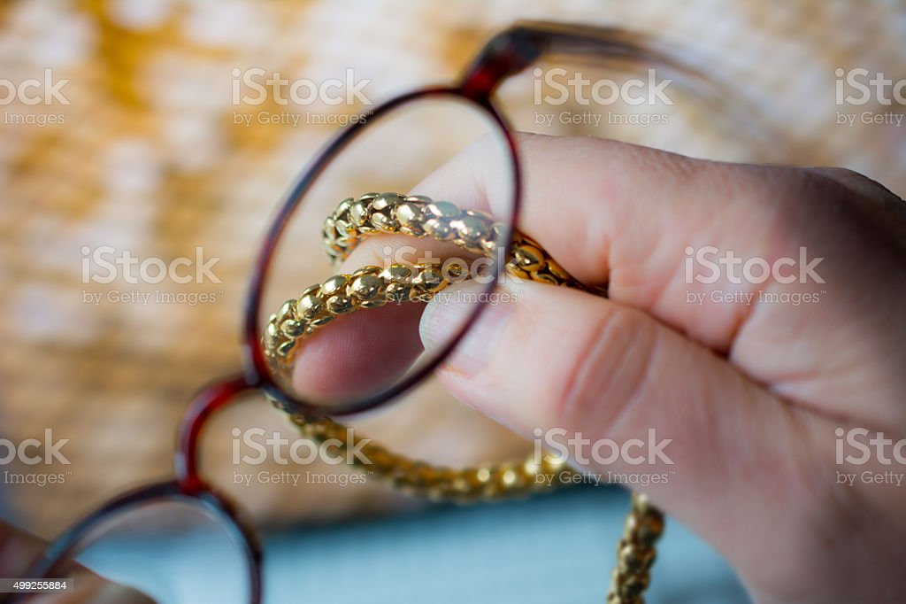 examining gold chain with reading glasses stock photo
