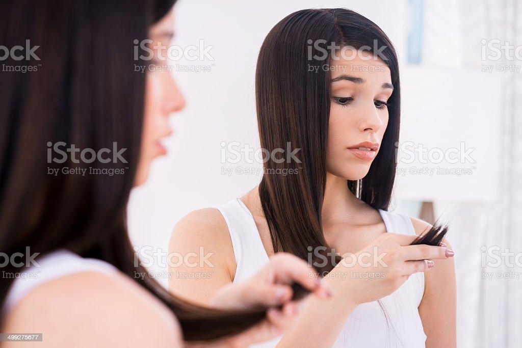 Examining her damaged hair. stock photo