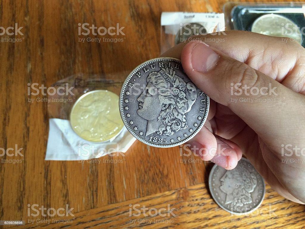 Examining Silver Dollar stock photo