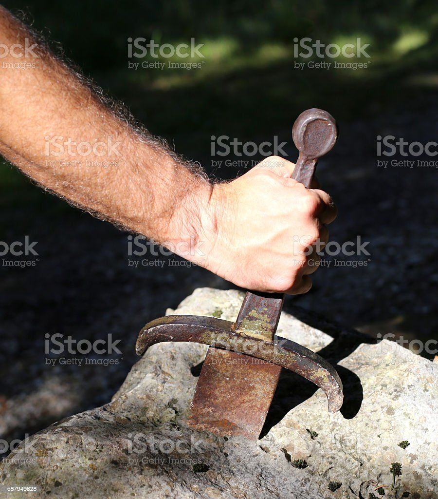 Excalibur sword in the stone and the hand of man stock photo