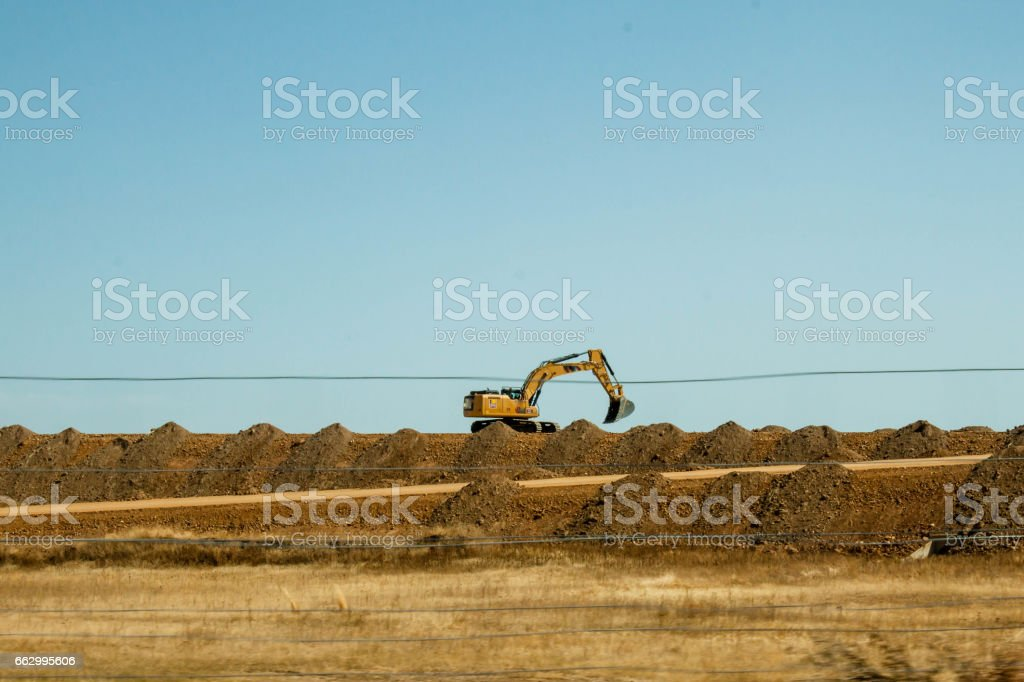 Excavation vehicle working on the construction of a road stock photo