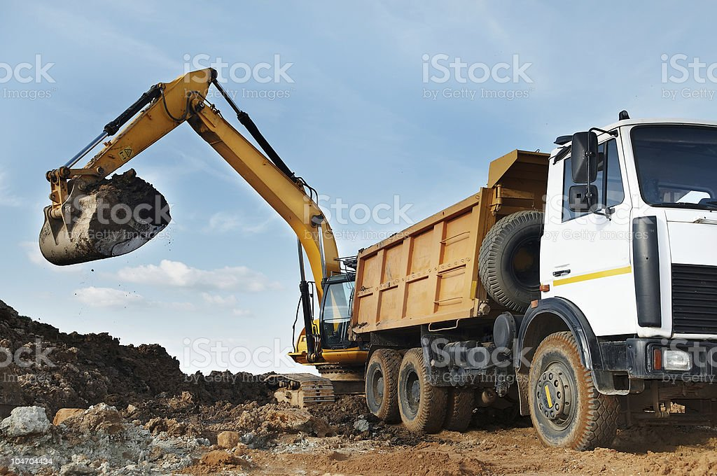 Excavator and dumper at loading works stock photo