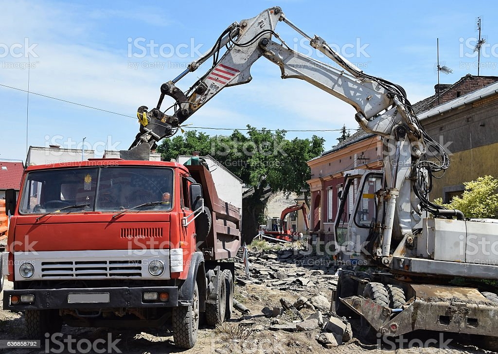 Excavator and truck at the road construction stock photo