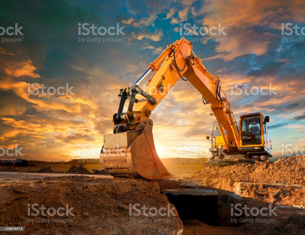 Excavator at a construction site against the setting sun. stock photo