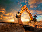 Excavator at a construction site against the setting sun.