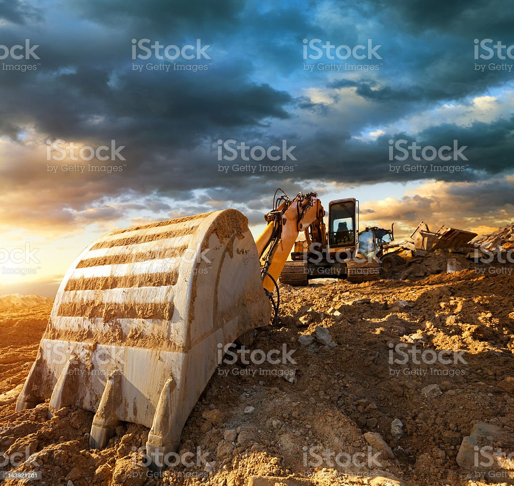 Excavator at a construction site against the setting sun stock photo