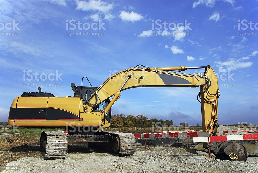 Excavator at construction site digging a hole stock photo