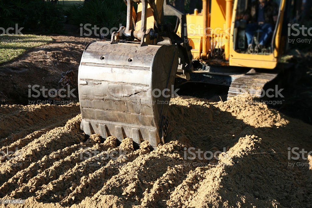 Excavator Back Hoe Spreading Dirt for Progress and Development royalty-free stock photo