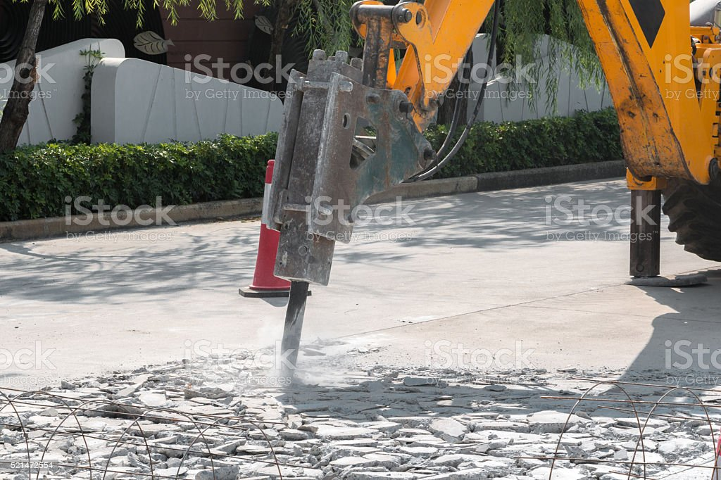 Excavator breaking and drilling the concrete road for repairing stock photo