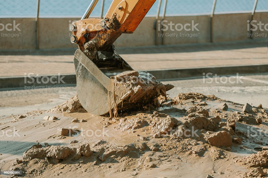Excavator cleaning mud from area with broken pipeline stock photo