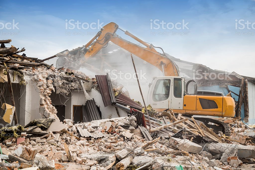 Excavator demolishing barracks stock photo