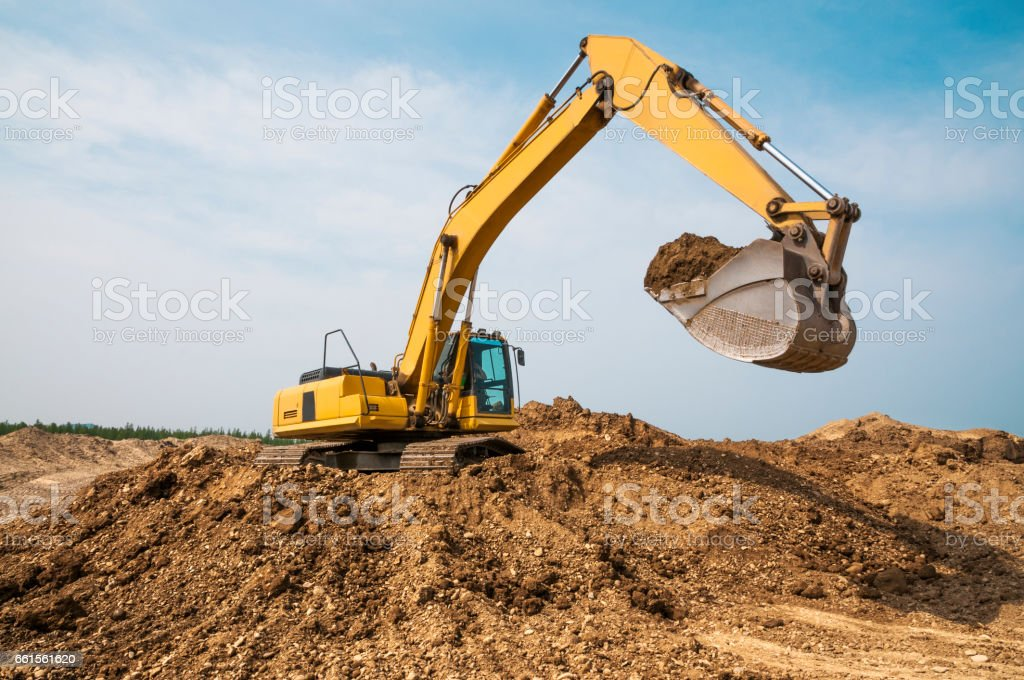 Excavator in anticipation of a truck dump, at the moment of a pause stock photo