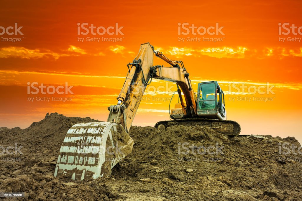 excavator in construction site on sunset sky stock photo