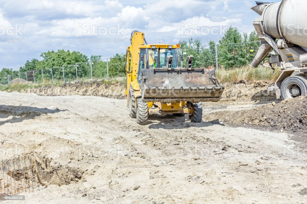 Excavator is carry bucket filled with fresh concrete stock photo