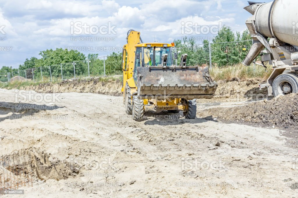 Excavator is carry bucket filled with fresh concrete. stock photo