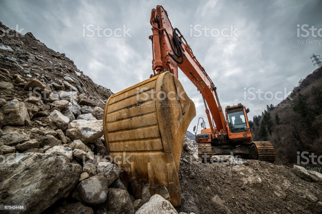 excavator is making pile of soil by pulling ground up on heap at construction site, project in progress stock photo