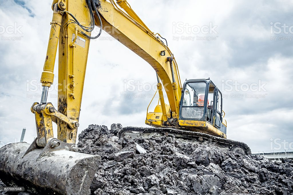 Excavator is preparing pile of ground for loading in truck. stock photo