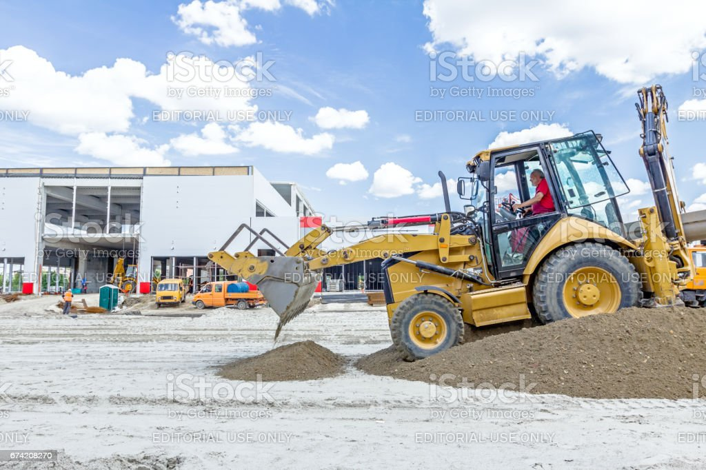 Excavator is unloading soil from his front bucket. stock photo