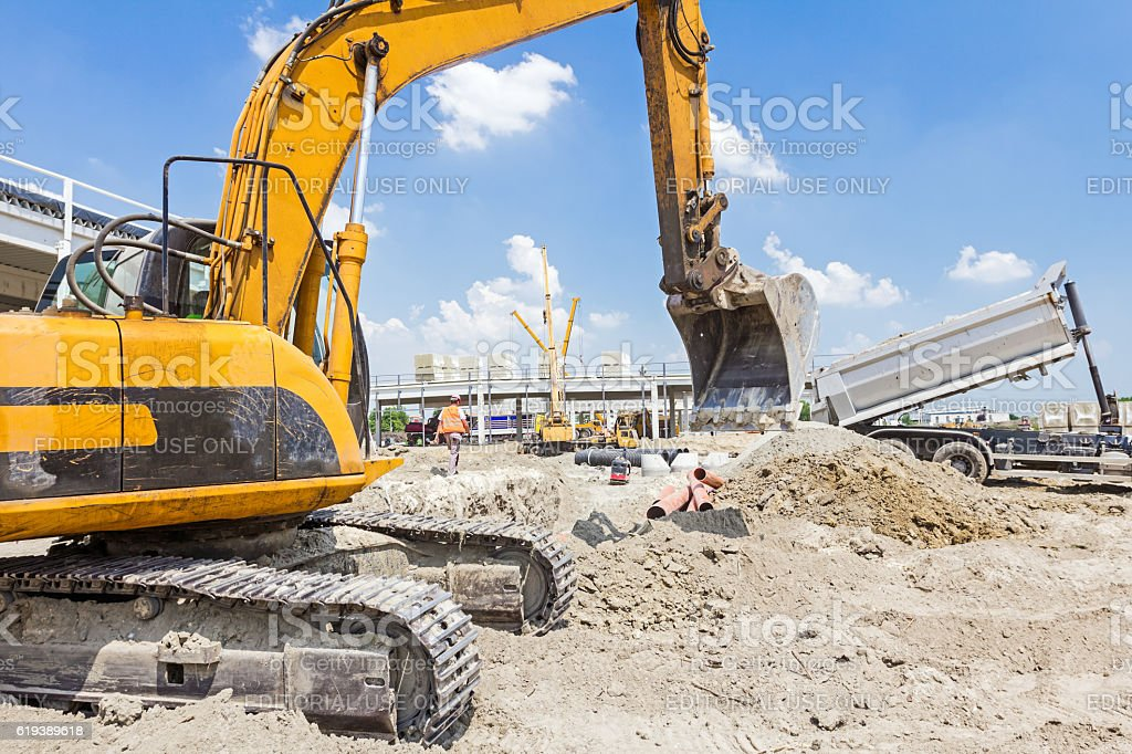 Excavator is working on construction site. Caterpillar in action stock photo