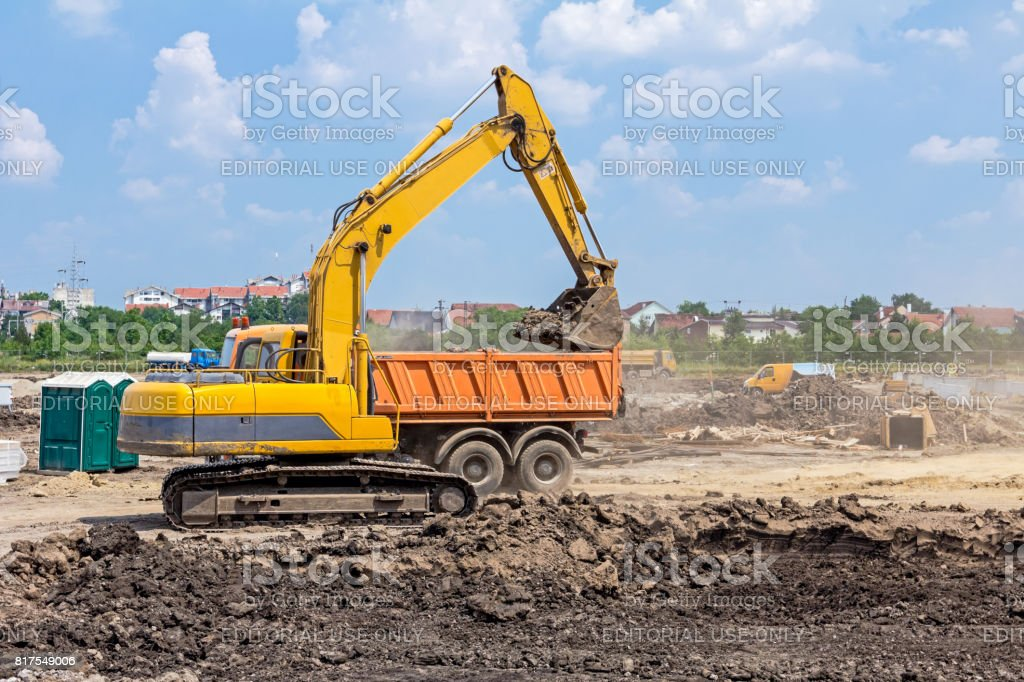 Excavator is working on construction site. Caterpillar in action. stock photo