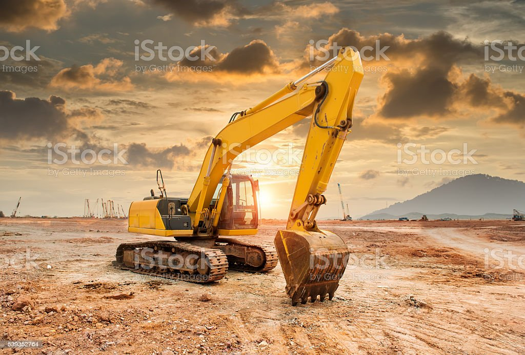 excavator loader machine during earthmoving works outdoors stock photo