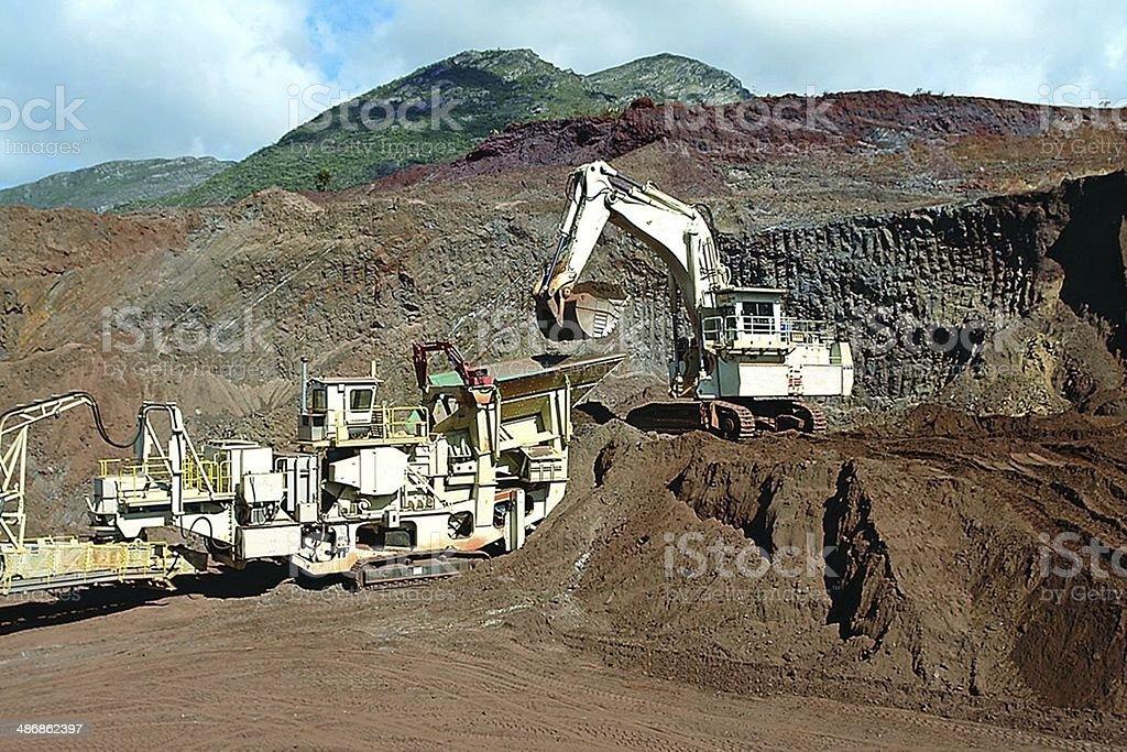 Excavator loading crusher iron mine stock photo
