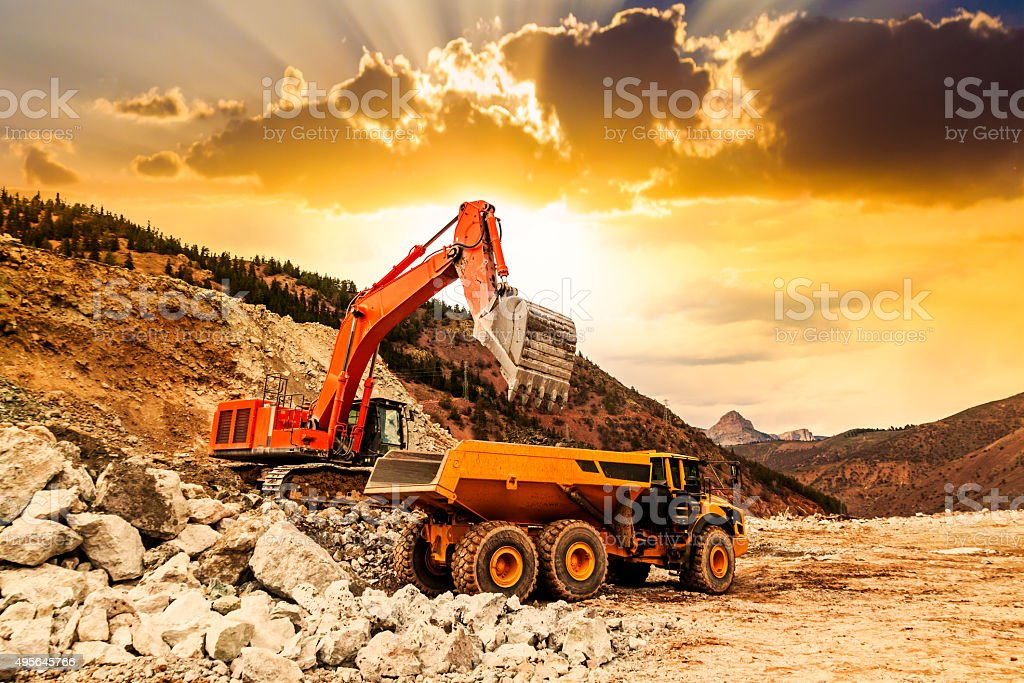 Excavator loading dumper truck at sunset stock photo