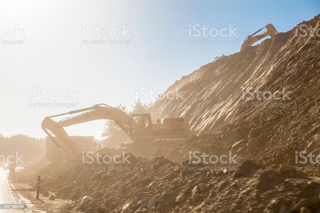 Excavator loading dumper truck on mining sit stock photo