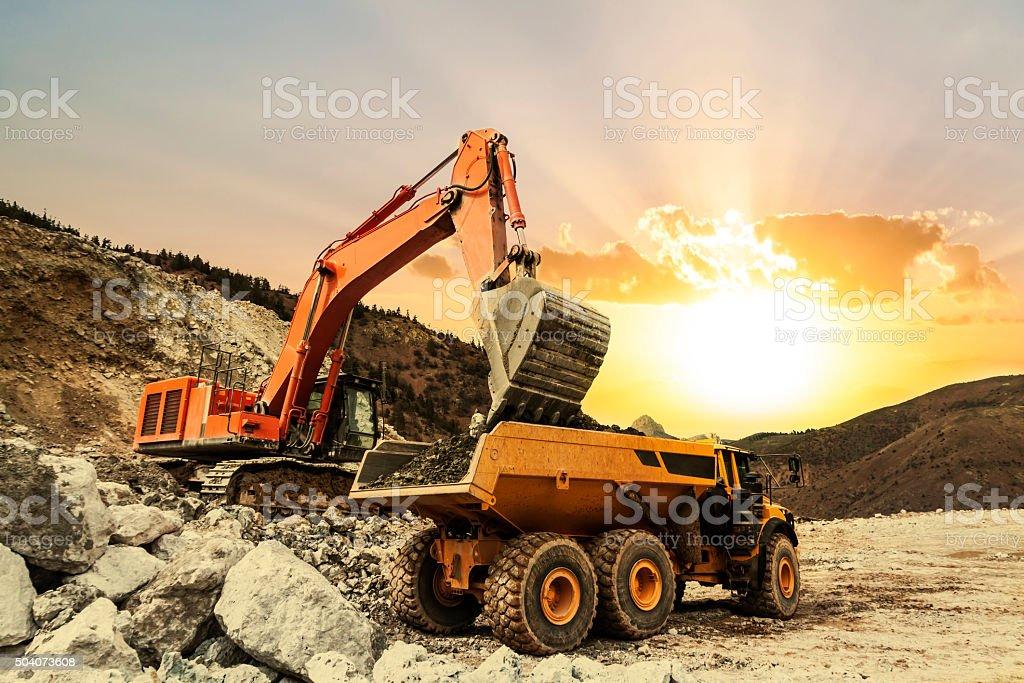 Excavator loading dumper truck on mining site stock photo