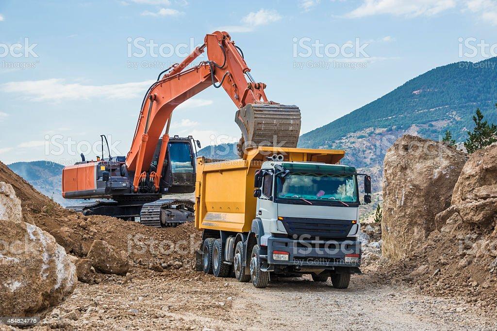 Excavator loading dumper truck stock photo