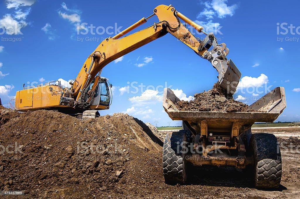 Excavator loading dumper truck tipper in sandpit stock photo