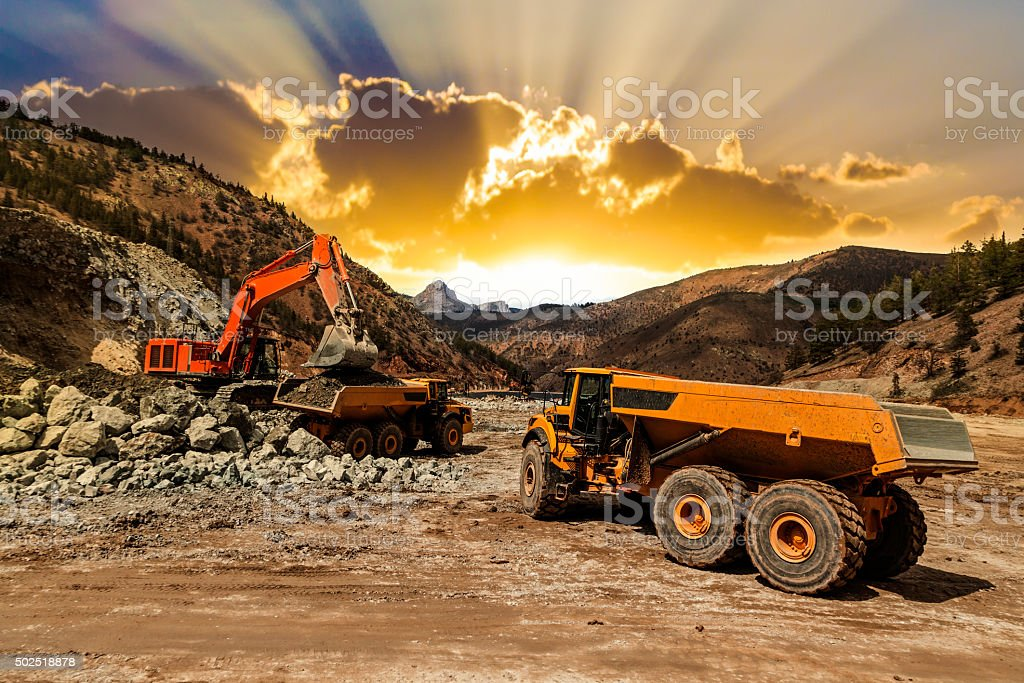 Excavator loading dumper trucks at sunset stock photo