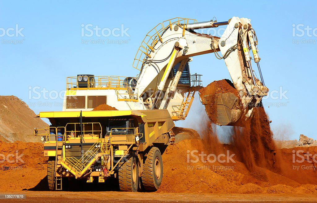 Excavator loading ore into a haul truck. stock photo