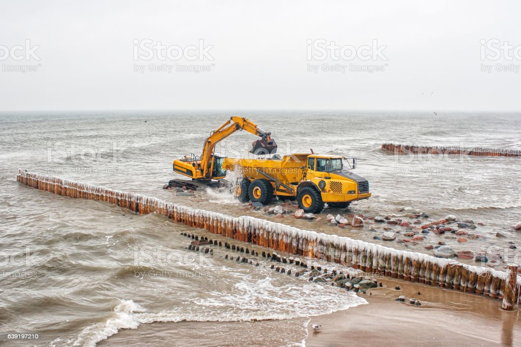 excavator loads a truck stones on the beach stock photo
