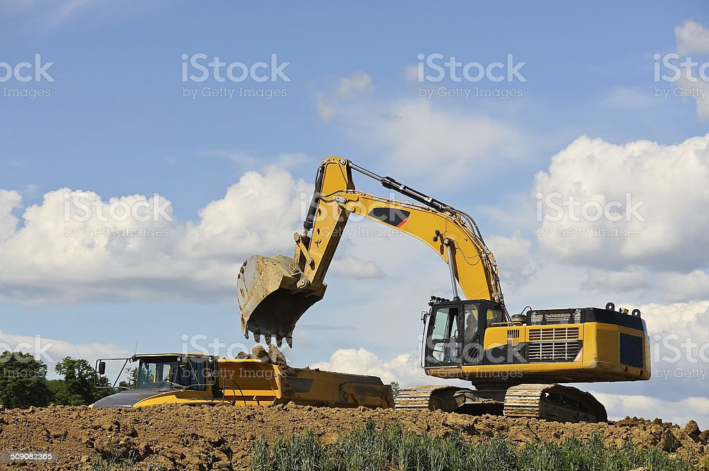 Excavator loads truck with Earth stock photo