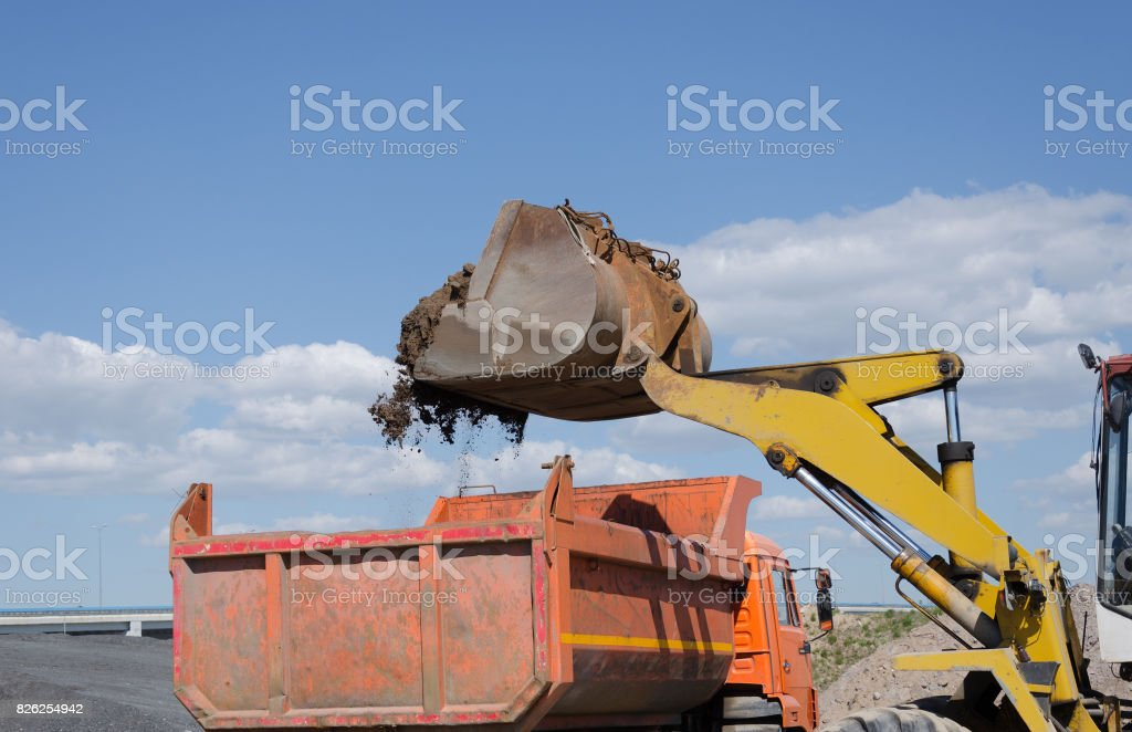 Excavator on gravel pile loading a truck stock photo
