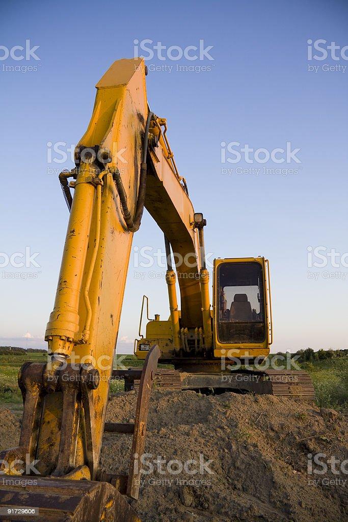 Excavator overlooking farmland at dusk stock photo