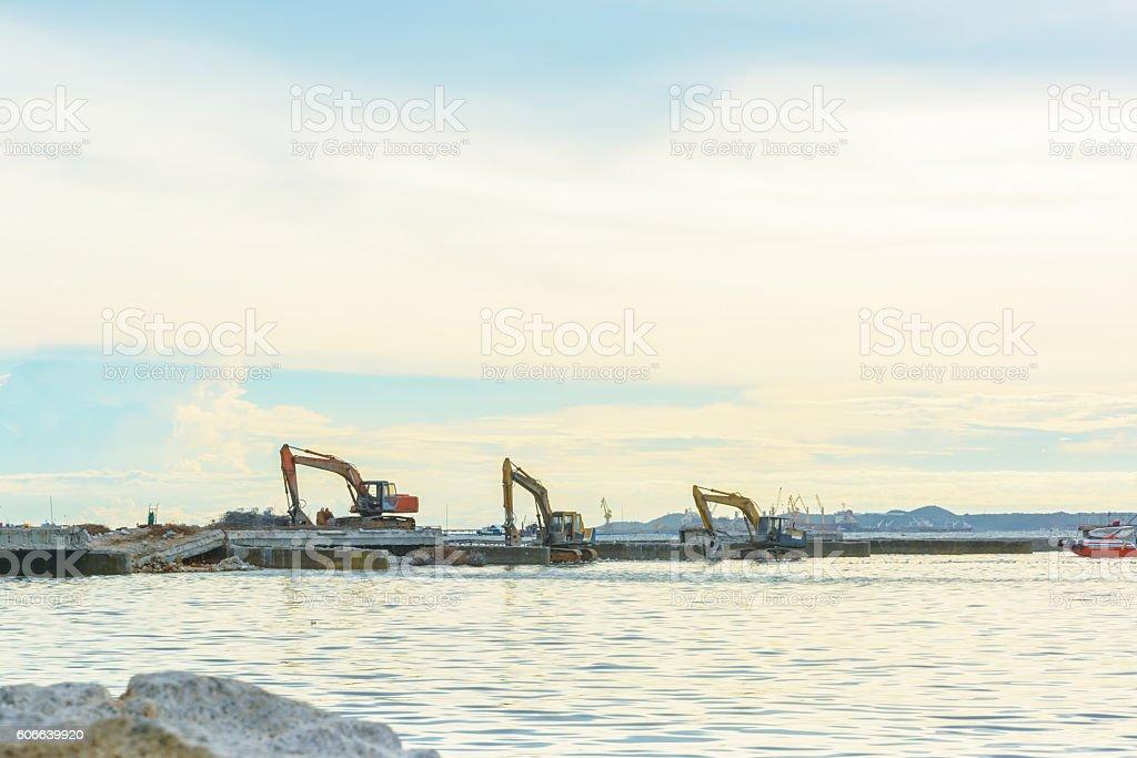 Excavator repair old bridge in a sea stock photo