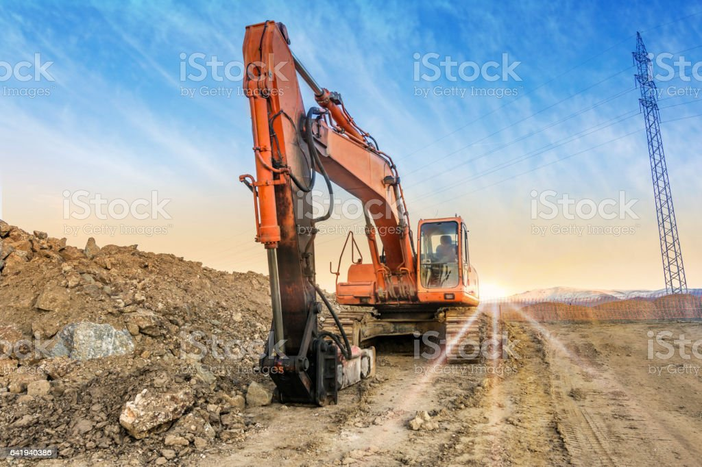 Excavadora con martillo hidráulico construyendo una carretera stock photo
