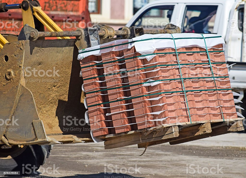 Excavator with paving stones stock photo